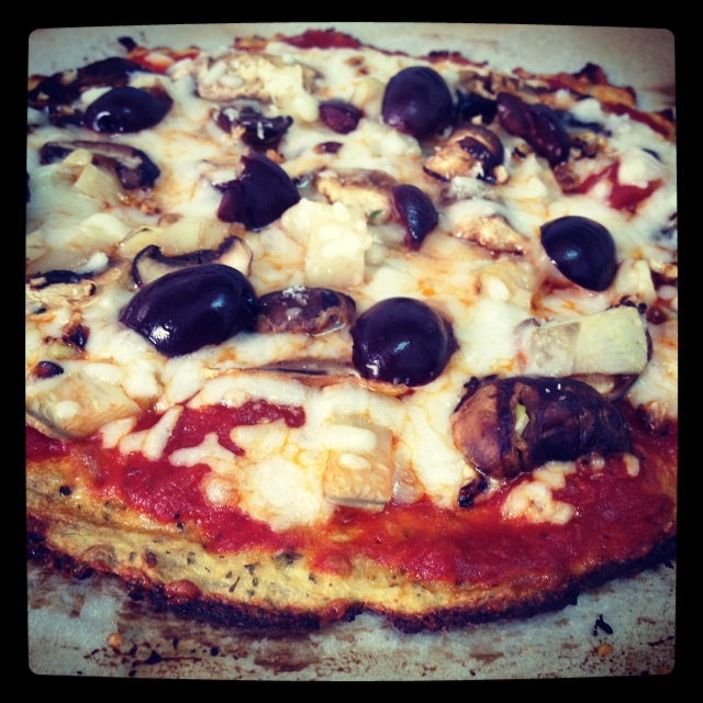Cauliflower crust pizza with tomato sauce, mushrooms, artichoke hearts, kalamata olives and mozzarella